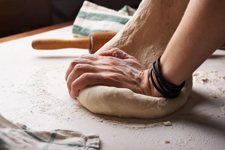 Imagem de alguém sovando massa de pão com fermentação natural